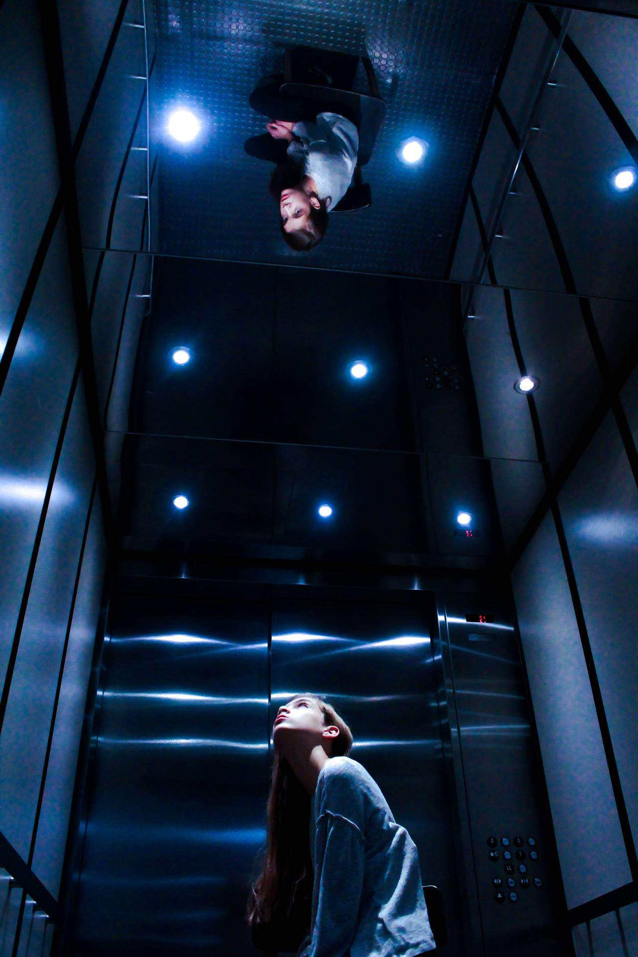 Girl looking up in an elevator at her reflection on the ceiling