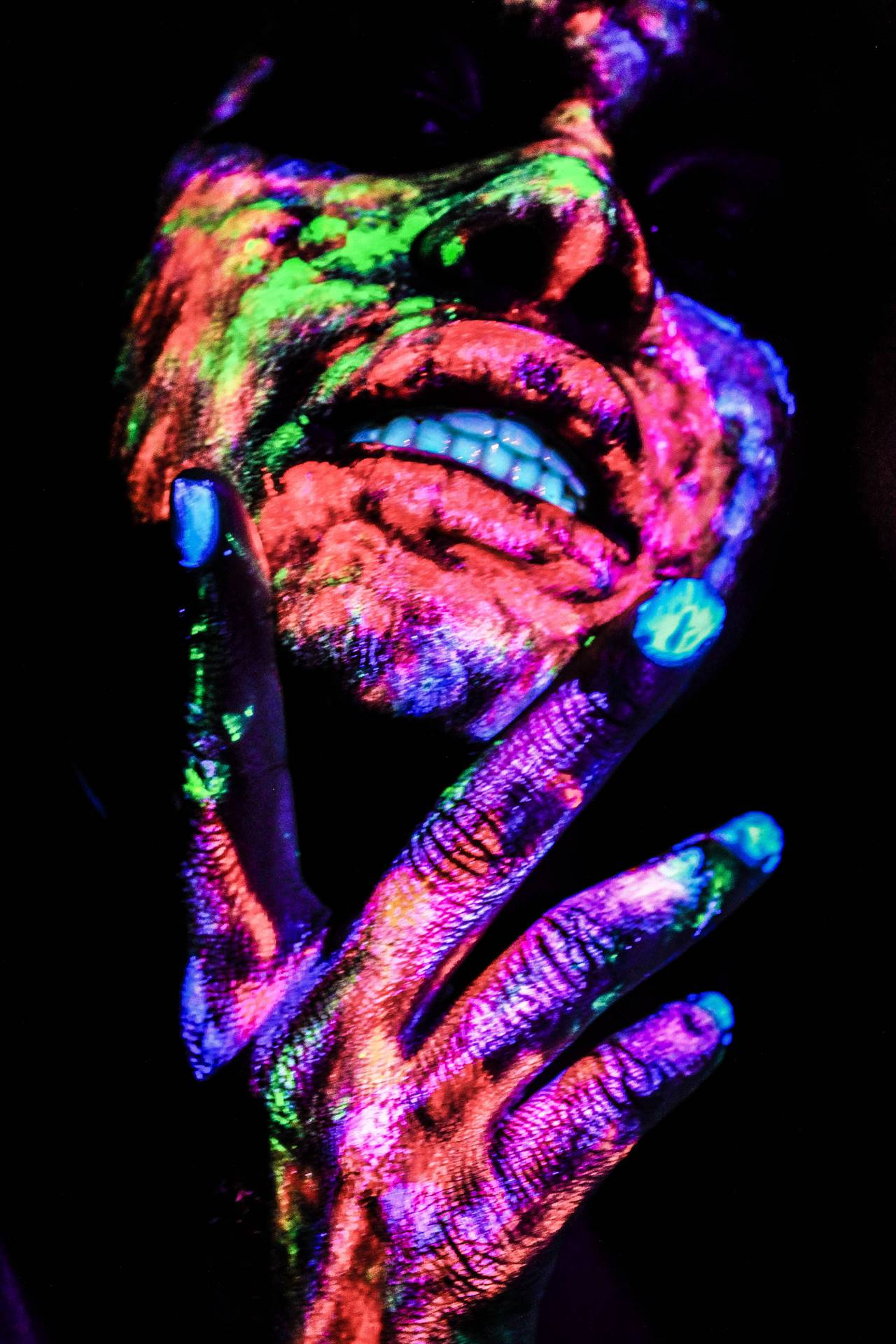 Colorful blacklight portrait of a person's face and hand