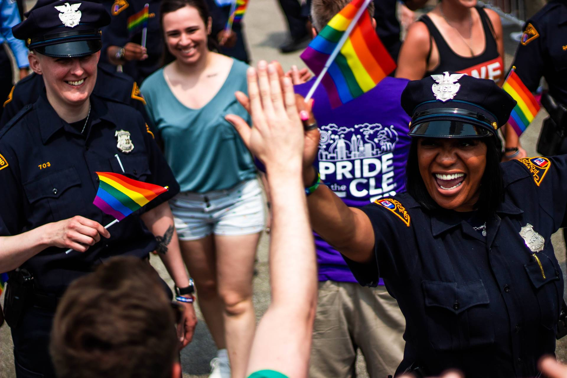 Person and a police officer high-fiving ini support of Pride Week