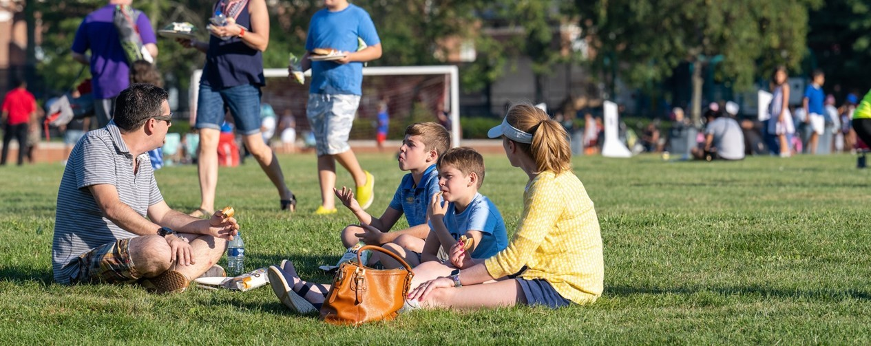 Family sitting in the grass at the Back-to-School Barbecue